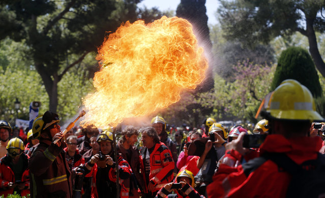 A fireman performs with fire during a protest against budget cuts in front of Catalunya's Parliament in Barcelona, April 10, 2014. (Photo by Albert Gea/Reuters)