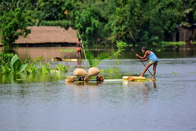 A man uses a makeshift raft to move his paddy to a safer place in a flooded area in Morigaon district in the northeastern state of Assam, India, July 16, 2019. (Photo by Anuwar Hazarika/Reuters)
