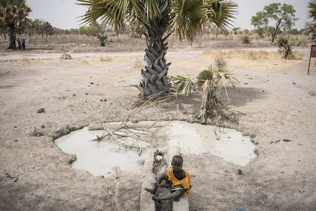 In this photo taken Sunday, March 12, 2017, a boy sits next to a fetid pool of water in Aweil, in South Sudan. (Photo by Mackenzie Knowles-Coursin/UNICEF via AP Photo)