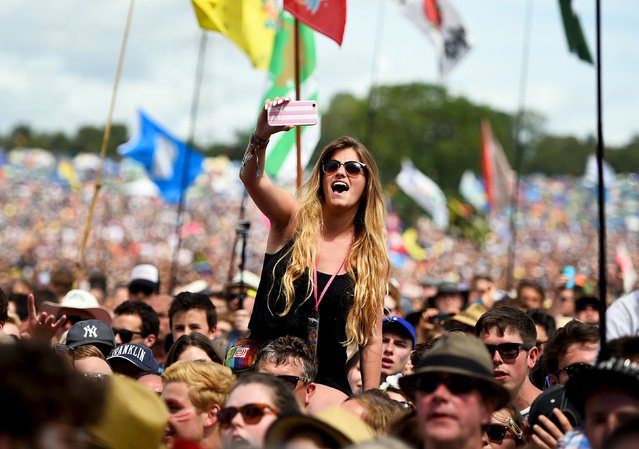 A reveller takes a selfie as George Ezra performs on the Pyramid stage at Worthy Farm in Somerset during the Glastonbury Festival in Britain, June 27, 2015. (Photo by Dylan Martinez/Reuters)