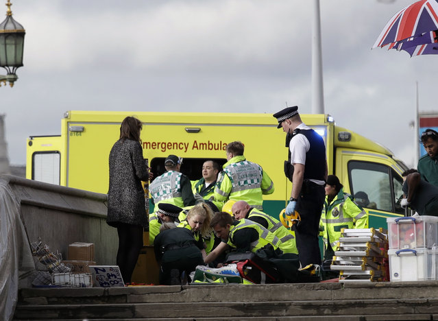 Emergency services staff provide medical attention close to the Houses of Parliament in London, Wednesday, March 22, 2017. (Photo by Matt Dunham/AP Photo)