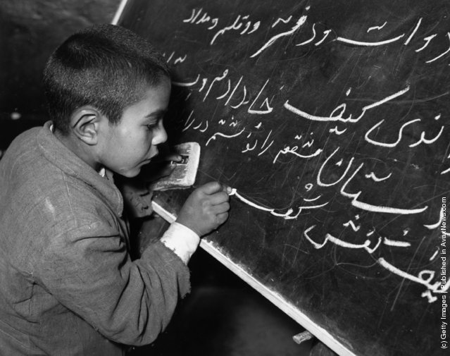1950:  A young Iranian boy learning how to write on a blackboard