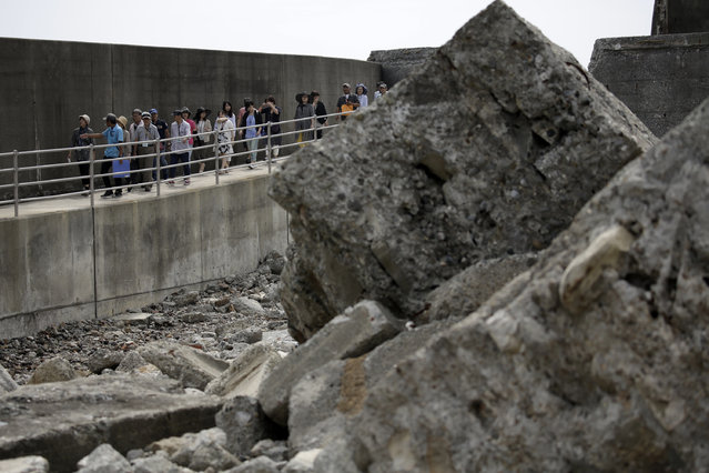 "In this June 29, 2015 photo, tourists visit Hashima Island, commonly known as Gunkanjima, which means ""Battleship Island"", off Nagasaki, Nagasaki Prefecture, southern Japan. (Photo by Eugene Hoshiko/AP Photo)"