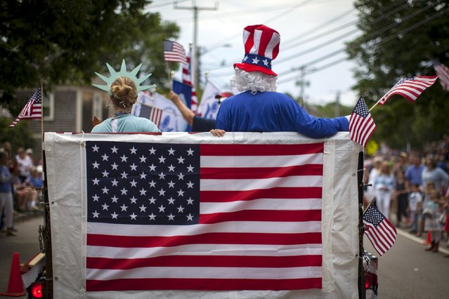 People in costumes ride on a float through Barnstable Village on Cape Cod during the annual 4th of July Parade in Barnstable, Massachusetts, July 4, 2015. (Photo by Mike Segar/Reuters)