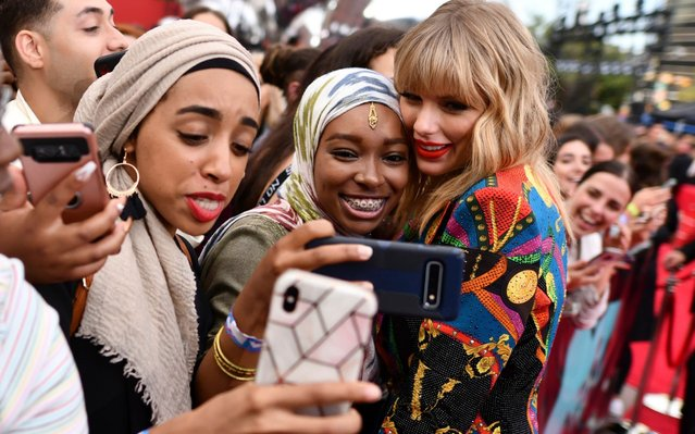 Taylor Swift, right, takes selfies with fans as she arrives at the MTV Video Music Awards at the Prudential Center on Monday, Aug. 26, 2019, in Newark, N.J. (Photo by Charles Sykes/Invision/AP Photo)