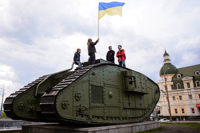 People hold a Ukrainian flag atop a World War I era MK V tank in Kharkiv, Ukraine, Wednesday, April 23, 2014. Ukraine's highly publicized goal to recapture police stations and government buildings seized by pro-Russia forces in the east produced little action on the ground Wednesday but ignited foreboding words from Moscow. (Photo by Olga Ivashchenko/AP Photo)