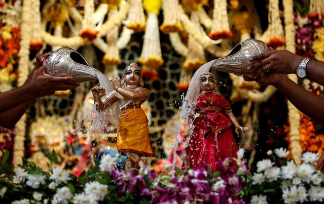 Hindu priests pour milk over the idols of Hindu Lord Krishna (L) and Radha, consort of Hindu Lord Krishna, during the festival of Janmashtami, marking the birth anniversary of Lord Krishna, in Ahmedabad, India, August 24, 2019. (Photo by Amit Dave/Reuters)
