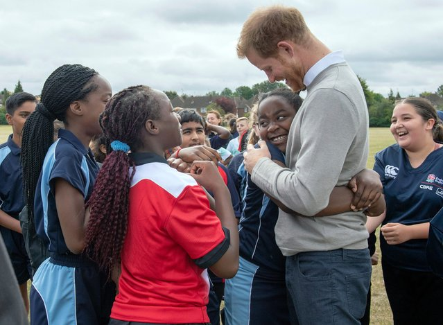 Britain's Prince Harry is hugged by a pupil during a visit the Rugby Football Union All Schools Programme at Lealands High School in Luton, England, Thursday, September 12, 2019. (Photo by Arthur Edwards/Pool Photo via AP Photo)