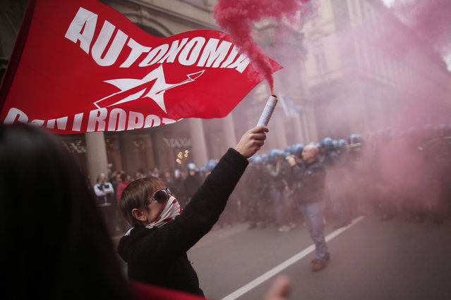 Anti-riot policemen face demonstrators in Turin during one of several rallies against unemployment and austerity in Italy for May Day, on May 1, 2014.  Activists lobbed smoke bombs at police, who charged against the demonstrators in an industrial city that has been badly hit by a painful two-year recession. Thousands also took part in a peaceful demonstration called by the main trade unions in Pordenone, where the closure of a nearby washing machine plant owned by Sweden's Electrolux is putting 1,300 jobs at risk. (Photo by Marco Bertorello/AFP Photo)