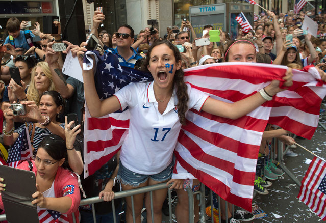 Lucie Keleman of New York's Westchester County cheers as U.S. Women's World Cup soccer champions make their way up Broadway to City Hall, during a ticker tape parade honoring the team Friday, July 10, 2015, in New York. (Photo by Bryan R. Smith/AP Photo)