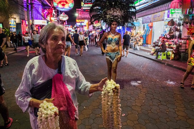 This photo taken on March 29, 2017 shows an elderly woman (L) offering flower garlands along Walking Street – a mile- long drag festooned with bars and clubs pouring out ear- crushing EDM music – in the Thai city of Pattaya. (Photo by Roberto Schmidt/AFP Photo)
