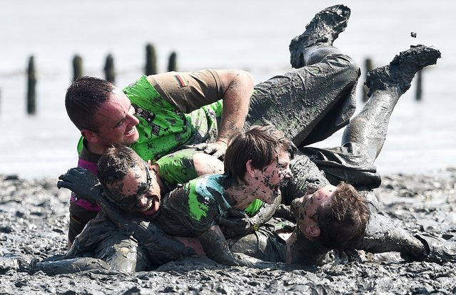 """Players celebrate a goal during a soccer match at the so called """"Wattoluempiade"""" (Mud Olympics) in Brunsbuettel at the North Sea, July 11, 2015. (Photo by Fabian Bimmer/Reuters)"""