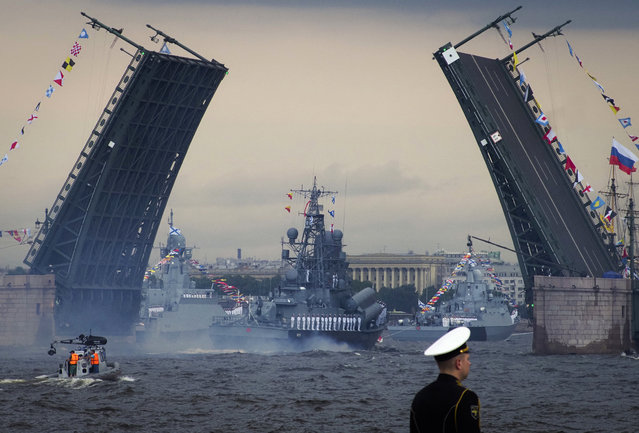 Warships float past the Dvortsovy (Palace) drawbridge rising above the Neva River during the Navy Day parade in St.Petersburg, Russia, Sunday, July 28, 2019. (Photo by Dmitri Lovetsky/AP Photo)