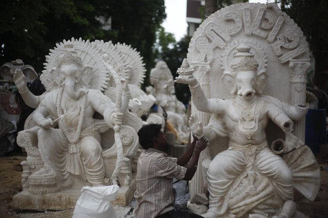 An Indian artisan prepares an idol of elephant headed Hindu god Ganesha in Ahmadabad, India, Thursday, July 9, 2015. The idols are being prepared ahead of the Ganesh Chaturti festival that will be celebrated in September. (Photo by Ajit Solanki/AP Photo)