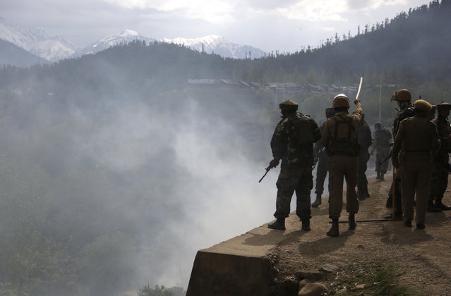 Indian army soldiers and police clash with Kashmiri villagers who were demanding the bodies of militants killed in a gun battle after a group of militants stormed a military camp in Panzgam, 127 Kilometers (79 miles) northwest of Srinagar, Indian controlled Kashmir, on Thursday, April 27, 2017. A 70-year-old civilian was killed and seven people were injured during an anti-India protest that erupted Thursday following a gun-battle that killed three Indian soldiers and two suspected rebels in disputed Kashmir, police said. (Photo by Mukhtar Khan/AP Photo)