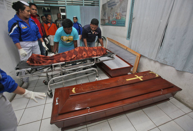 Medical workers prepare to put the body of one of the victims of the eruption of Mt. Sinabung into a coffin at a hospital in Kabanjahe, North Sumatra, Indonesia, Sunday, May 22, 2016. (Photo by Binsar Bakkara/AP Photo)