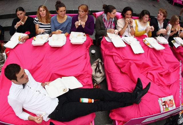 People wait in beds during the The World's Biggest Breakfast in Bed Guinness World Record Attempt at Martin Place in Sydney, Australia
