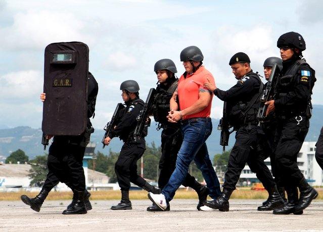 Policemen escort suspected drug trafficker Jairo Orellana as he is brought before the media, before being extradited to the U.S., at Aurora international airport in Guatemala City, Guatemala, July 24, 2015. Guatemalan suspected drug trafficker Orellana, linked to powerful Mexican cartels, was extradited Friday to the United States, on charges of conspiracy for the smuggling of drugs, local media reported. (Photo by Josue Decavele/Reuters)