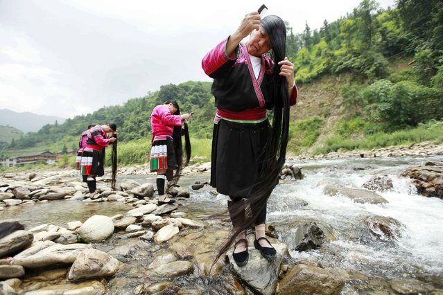 Ethnic Yao minority women brush their long hair near a creek, in Huangluo village of Guilin, Guangxi Zhuang Autonomous Region, China, July 23, 2015. The village, known for the long hair of its female residents, attracts about 80,000 tourists a year. More than 80 women in the village have hair longer than 1.4 metres, with the longest reaching 2.2 metres, according to local media. (Photo by Reuters/Stringer)
