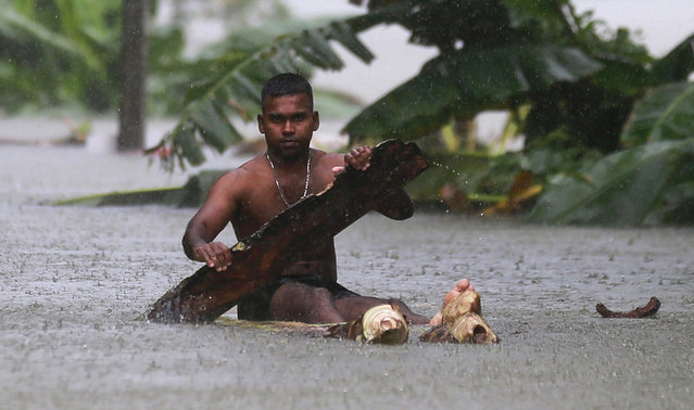 A Sri Lankan man rows a makeshift raft on a flooded road in Wehangalla village in Kalutara district, Sri Lanka, Saturday, May 27, 2017. Sri Lanka's military said Saturday that it is doubtful there could be any survivors two days after torrents of mud triggered by heavy rain covered homes in southern and western parts of the country. (Photo by Eranga Jayawardena/AP Photo)