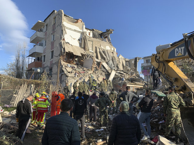 Rescuers search at a damaged building after a magnitude 6.4 earthquake in Thumane, western Albania, Tuesday, November 26, 2019. Rescue crews used excavators to search for survivors trapped in toppled apartment buildings after a powerful pre-dawn earthquake in Albania killed at least six people and injured more than 300. (Photo by Visar Kryeziu/AP Photo)