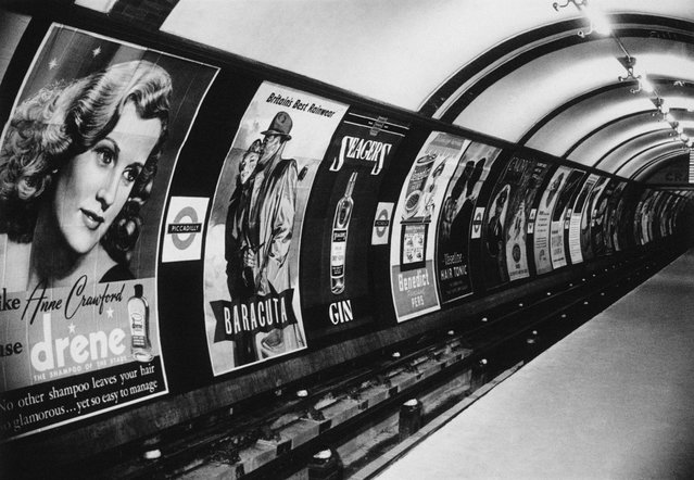 Shampoo, raincoats and gin are some of the products advertised in the posters that line the tunnel wall at the Piccadilly underground station, London in 1949. (Photo by Hulton-Deutsch/Hulton-Deutsch Collection/Corbis via Getty Images)