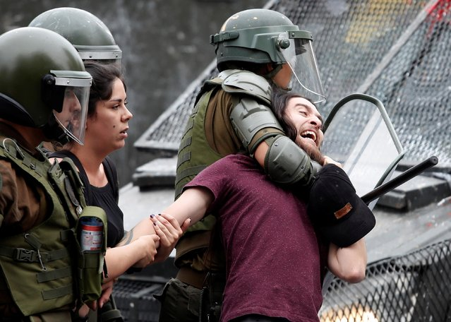 Police detain a demonstrator during a protest against Chile's government in Santiago, Chile on December 2, 2019. (Photo by Goran Tomasevic/Reuters)