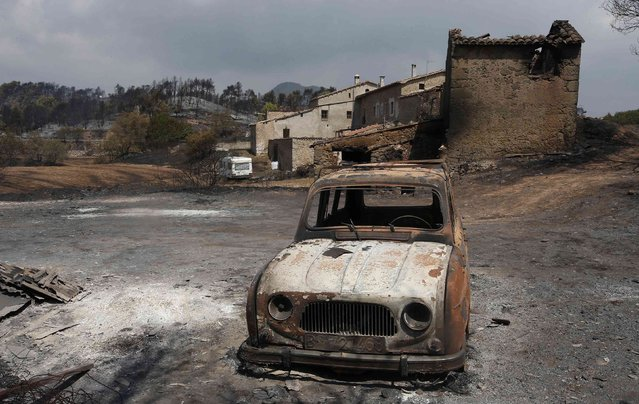 A burnt car is seen in front of a farm after a forest fire near Montserrat in Sant Salvador de Guardiola, in the northeastern region of Catalonia, Spain, July 27, 2015. The fire, which broke out near the town of Odena, has burned over a thousand hectares, and forced the evacuation of over 800 people, according to local authorities. (Photo by Gustau Nacarino/Reuters)