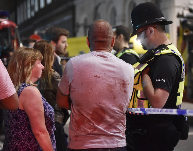People speak with police officers after an incident near London Bridge in London on June 4, 2017 following a terrorist attack on London Bridge and Borough Market. (Photo by Hannah McKay/Reuters)