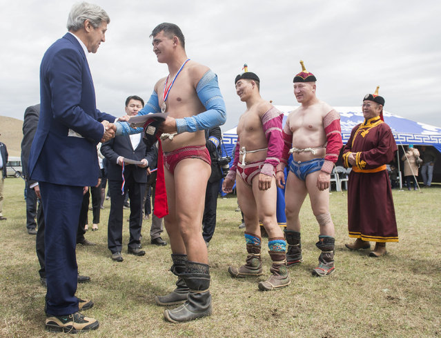 US Secretary of State John Kerry awards the winners of a traditional Mongolian wrestling match after watching a Naadam ceremony, a competition which traditionally includes horse racing, Mongolian wrestling and archery, in Ulan Bator, Mongolia, June 5, 2016. (Photo by Saul Loeb/Reuters)
