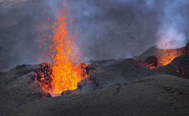 "Lava erupts from the Piton de la Fournaise ""Peak of the Furnace"" volcano, on the southeastern corner of the Indian Ocean island of Reunion Saturday, August 1, 2015. Spewing red-hot lava, one of the most active volcanoes in the world is currently erupting on this Indian Ocean island, where the world's attention has been focused since a wing fragment believed to be from the missing Malaysian jet was discovered washed up on a beach. (Photo by Ben Curtis/AP Photo)"