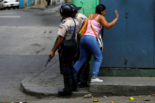 A woman walks among riot police officers after a protest over food shortage and against Venezuela's government in Caracas, Venezuela, June 10, 2016. (Photo by Ivan Alvarado/Reuters)