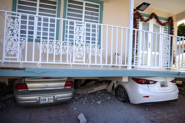 Cars are crushed under a home that collapsed after an earthquake hit Guanica, Puerto Rico, Monday, January 6, 2020. A 5.8-magnitude quake hit Puerto Rico before dawn Monday, unleashing small landslides, causing power outages and severely cracking some homes. There were no immediate reports of casualties. (Photo by Carlos Giusti/AP Photo)