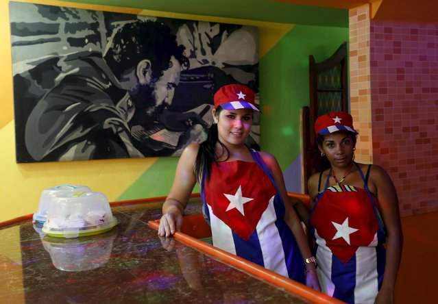 Neiky (L), 18, and Legna, 21,  waitresses of a private cafeteria pose for a photo near a painting of Cuba's former president Fidel Castro in Havana April 14, 2015. (Photo by Reuters/Stringer)