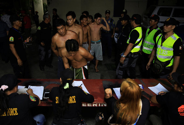 """People queue as they are interviewed by town volunteers while members of the Philippine National Police stand guard during the """"Rid the streets Of Drinkers and Youth"""" operation in Las Pinas city, metro Manila, Philippines June 1, 2016. (Photo by Romeo Ranoco/Reuters)"""