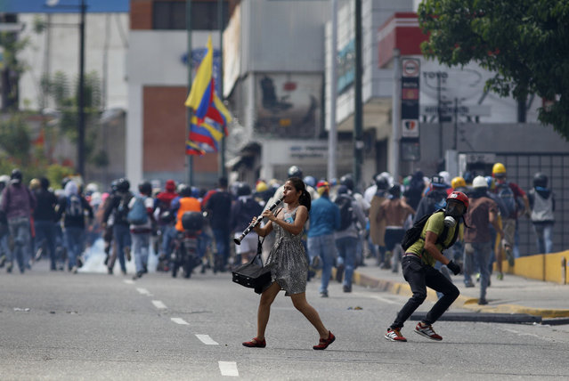 A young woman plays her clarinet in the midst of clashes between anti-government demonstrators and security forces, during a protest in Caracas, Venezuela, Thursday, July 6, 2017. The demonstrators were marching towards the Supreme Court when they were intercepted by authorities. Opposition protests demanding new elections and decrying triple-digit inflation, food shortages and worsening crime continue as President Nicolas Maduro pushes forward with his plan to draft a new constitution. (Photo by Ariana Cubillos/AP Photo)