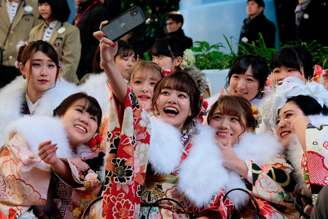 Twenty-year-old women draped in traditional kimonos gather for their 'Coming-of-Age Day' ceremony at the Tokyo Disneyland in Urayasu, eastern suburb of Tokyo on January 13, 2020. (Photo by Kazuhiro Nogi/AFP Photo)