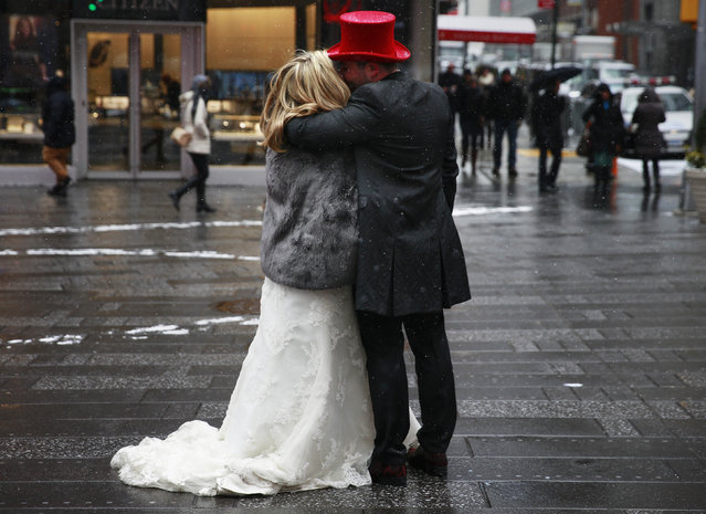 A couple embraces during light snowfall at Times Square in New York January 6, 2015. (Photo by Shannon Stapleton/Reuters)