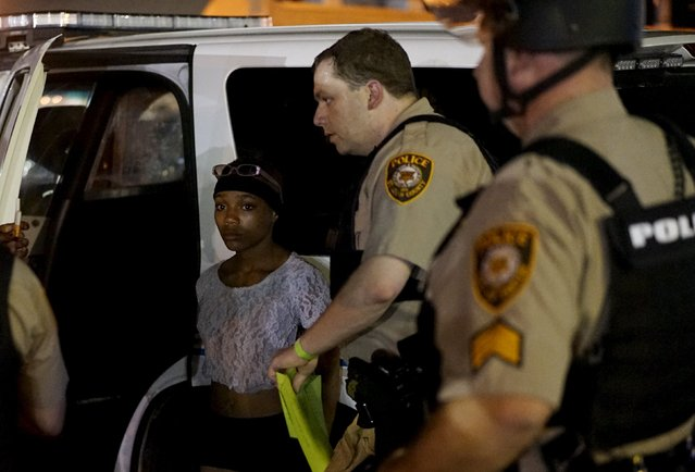 A police officer holds a protester who was detained in Ferguson, Missouri, August 10, 2015. (Photo by Rick Wilking/Reuters)
