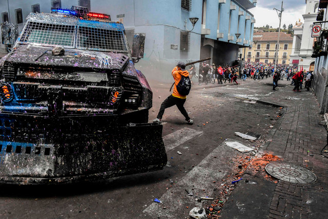 A demonstrator hits an armoured vehicle with a stick during clashes with riot police in Quito, as thousands march against Ecuadorean President Lenin Moreno's decision to slash fuel subsidies, on October 9, 2019. Unions and other groups alongside thousands of farmers and indigenous people are expected in the streets of the capital Quito. Protests and clashes erupted in Ecuador a week ago, after the government doubled fuel prices as part of an agreement with the International Monetary Fund to obtain loans despite its high public debt. (Photo by Martin Bernetti/AFP Photo)