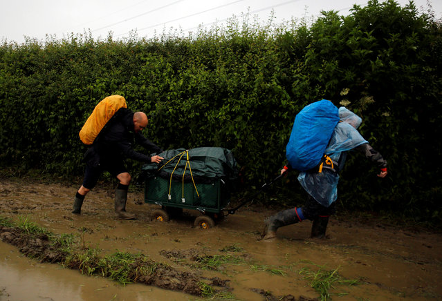 Revellers carry their belongings as they arrive at Worthy Farm in Somerset for the Glastonbury Festival, Britain, June 22, 2016. (Photo by Stoyan Nenov/Reuters)