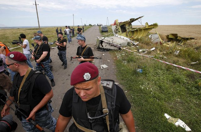 "Armed pro-Russian separatists stand guard at a crash site of Malaysia Airlines Flight MH17, near the village of Hrabove, Donetsk region July 20, 2014. Ukraine on Sunday accused separatist rebels of hiding evidence that a Russian missile was used to shoot down the Malaysian airliner, while Britain said Moscow faced ""pariah"" status and the threat of further economic sanctions. (Photo by Maxim Zmeyev/Reuters)"
