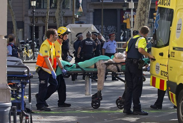 Mossos d'Esquadra Police officers and emergency service workers move an injured after a van crashes into pedestrians in Las Ramblas, downtown Barcelona, Spain, 17 August 2017. (Photo by Quique Garcia/EPA/Rex Features/Shutterstock)