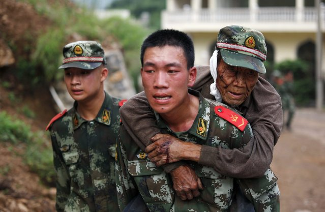 A paramilitary policeman carries an elderly man on his back after an earthquake hit Ludian county of Zhaotong, Yunnan province August 3, 2014. The magnitude 6.5 earthquake struck southwestern China on Sunday, killing at least 150 people in the remote mountainous area of Yunnan province, causing some buildings, including a school, to collapse, Xinhua News Agency reported. (Photo by Reuters/China Daily)