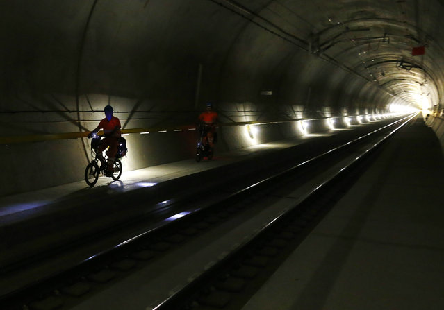 Workers cycle next to the railway tracks at the NEAT Gotthard Base tunnel near Amsteg September 3, 2014. (Photo by Ruben Sprich/Reuters)