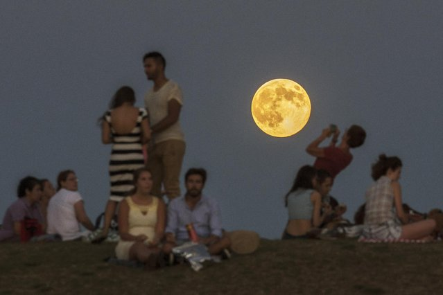 People gather in the park as a perigee moon, also known as a supermoon, rises in Madrid, Sunday, August 10, 2014. (Photo by Andres Kudacki/AP Photo)