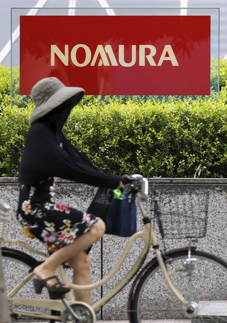 A woman cycles past a sign of Nomura Holdings in Tokyo July 29, 2015. (Photo by Toru Hanai/Reuters)