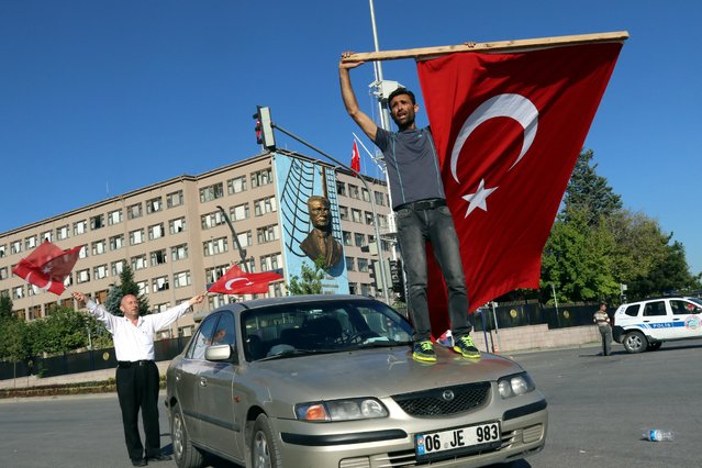 A man waves a Turkish flag as people protest against a coup near the Turkish military headquarters, in Ankara, Turkey, Saturday, July 16, 2016. (Photo by Ali Unal/AP Photo)