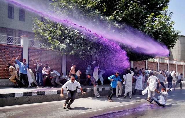 Colored water from a police water cannon hits Kashmiri government employees as they shout slogans during a protest in Srinagar, India, Thursday, August 21, 2014. Police used force to disperse Kashmiri government employees during the protest demanding regularization of contractual jobs and a hike in salary. (Photo by Mukhtar Khan/AP Photo)
