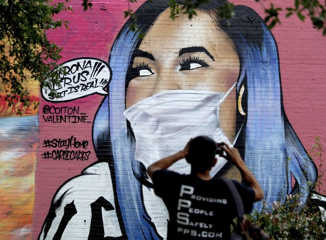 A man photographs a mural of Cardi B that was updated by the artist Colton Valentine to include a face mask to reflect the coronavirus pandemic, in San Antonio, Monday, March 30, 2020. Due to the COVID-19 outbreak, San Antonio an many other Texas cities are under stay-at-home orders. (Photo by Eric Gay/AP Photo)